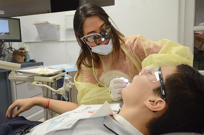 Arriba, una estudiante de Medicina Dental ofrece servicios gratuitamente a un niño, como parte de las actividades celebradas en el Recinto de Ciencias Médicas. (Foto Ricardo Alcaraz-Diálogo)