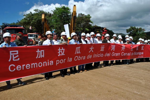 Ejecutivos de la empresa china HKDN-Group e integrantes de la Comisión Nicaragüense del Gran Canal Interoceánico, detrás de una gran pancarta, el 22 de diciembre de 2014, en la localidad de Brito Rivas, en la costa del océano Pacífico, en el acto de comienzo formal de la gigantesca obra que partirá en dos el país. Crédito: Mario Moncada/IPS