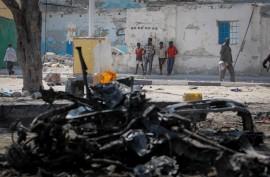 En grupo de somalíes miran un auto destruido por una bomba luego de un ataque suicida del grupo extremista al-Shabab en el 2013, quienes se autoproclamaron autores de la masacre en el Colegio Universitario de Garissa en Kenia. (Stuart Price / Flickr Commons)