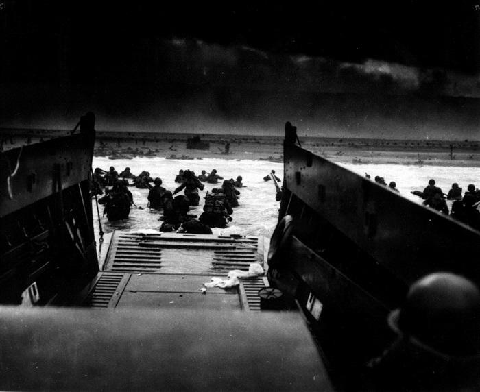 """Soldados estadounidenses desembarcan de un bote de la Guardia Costera en las costas de Francia bajo intenso fuego de ametralladoras alemanas durante el """"Día-D"""" el 6 de junio de 1944. (Administración de los Archivos Nacionales)"""