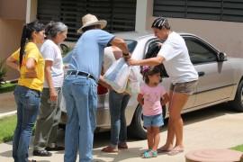 Miembros del Banco de Alimento de Puerto Rico hacen entrega de unas bolsas con alimentos a una comunidad orocoveña. (Michelle Estades)