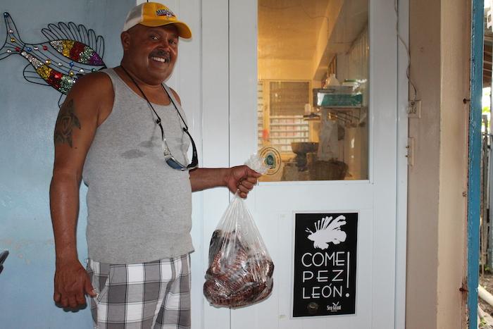 Pescador de Guánica con una bolsa de peces leones. (Michelle Estades/ Diálogo)