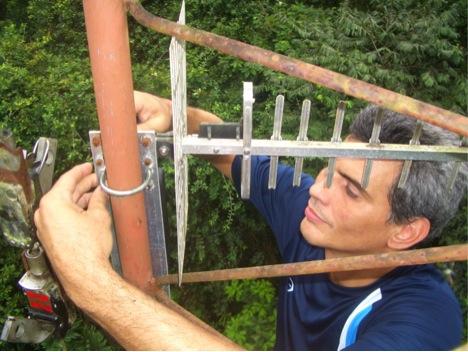"""El profesor Corrada, del Departamento de Ciencias de Cómputos de la UPR-Río Piedras, colocando el equipo del proyecto """"Arbimon"""". (Suministrada)"""