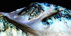 Delgadas rayas negras fluyen cuesta abajo en Marte, en lo que la NASA ha identificado como un flujo de agua de temporada en suelo marciano. (NASA/JPL-Caltech/Univ. of Arizona)