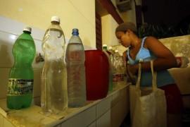 Una residente en el municipio capitalino de Habana del Este organiza en su hogar los envases con agua potable que acaba de acarrear desde la calle, tras días sin suministro del recurso en su vivienda en la capital de Cuba. La recolección de agua para el consumo doméstico se suma a las tareas cotidianas de las mujeres en La Habana. Crédito: Jorge Luis Baños/IPS