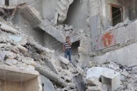 Residente de la ciudad siria de Aleppo en medio de un edificio bombardeado por las fuerzas del presidente Bashar al-Assad. Credit: Zak Brophy/IPS.