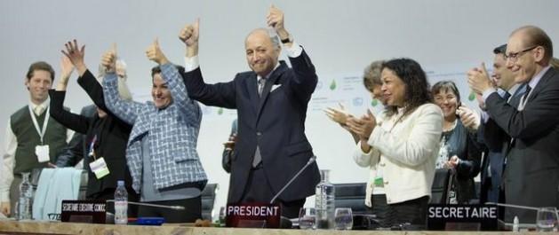El presidente de la COP21, Laurent Fabius, en el centro, y otros líderes de la cumbre de París aplauden y hacen señales de victoria al lograrse el histórico acuerdo universal y vinculante para afrontar el cambio climático. Crédito: CMNUCC