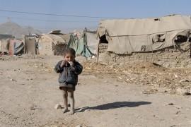 Un pequeño refugiado afgano come un pedazo de dulce frente a la tienda de campaña que ocupa su familia. Crédito: DVIDSHUB/CC-BY-2.0