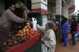 Una mujer paga la compra de productos agrícolas en un mercado administrado por trabajadores por cuenta propia, donde se venden frutas y verduras de la cooperativa Nicomedes Corvo, en el barrio de El Vedado de La Habana, en Cuba. Crédito: Jorge Luis Baños/IPS