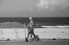 Bañista camina por la zona de Puerta de Tierra donde se construye el Paseo Lineal. (Doel Vázquez)