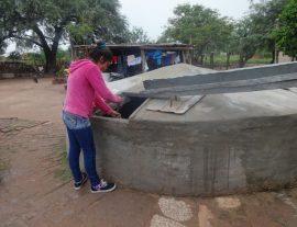 La joven Jésica Garay, estudiante de magisterio y madre de un bebe, saca agua de lluvia de la cisterna familiar instalada al lado de su humilde vivienda, en el municipio rural de Corzuela, en la provincia de Chaco, en el norte de Argentina. Crédito: Fabiana Frayssinet/IPS