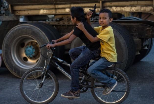 Dos niños transitan en una bicicleta por una calle del centro de Ciudad de Guatemala, el pasajero con una pistola de juguete en sus manos. Las armas son parte cotidiana en las urbes de este país centroamericano. Crédito: Ximena Natera/Pie de Página