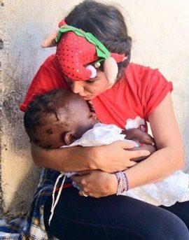 Karla Michelle De León y un pequeño durante misión voluntaria. (Suministrada)