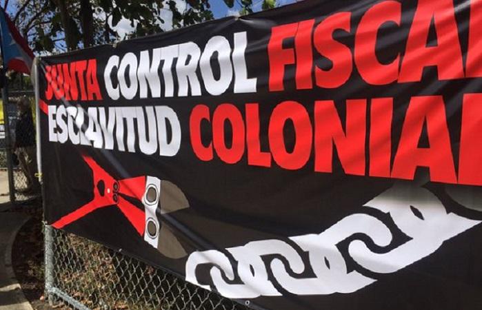 Imagen de un cruzacalle de protesta en alusión a la junta de control fiscal. (Radio Isla)