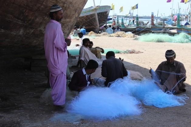Pescadores en la ciudad portuaria de Karachi, en el sur de Pakistan, revisan sus redes. Crédito: Zofeen Ebrahim/IPS.