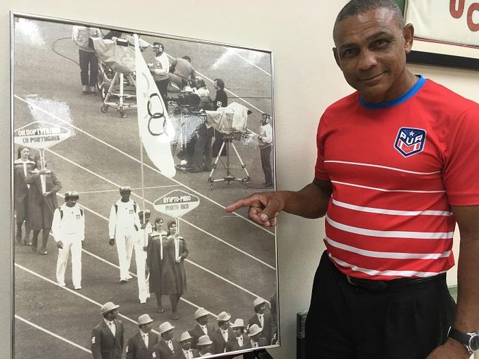 Alberto Mercado muestra la foto en la que él carga la bandera olímpica durante el desfile de los Juegos Olímpicos en Moscú, 1980. (Suministrada)