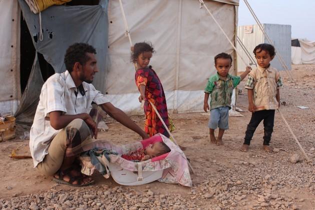 Un hombre yemení cuida a un bebé en el campamento de Obock. Crédito: James Jeffrey / IPS.