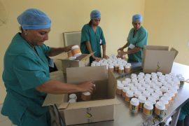 Tres mujeres trabajan en el envasado y etiquetado de píldoras de espirulina, en la planta de producción, de la empresa estatal Genix-Labiofam, en la localidad de Zaragoza, en Cuba.  (Jorge Luis Baños/IPS)
