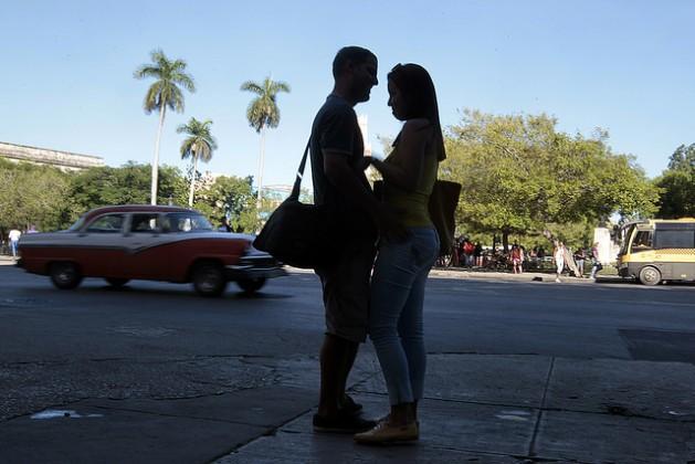 Una pareja de jóvenes, en actitud cariñosa mientras aguarda la llegada de un bus en el municipio de Centro Habana, en la capital de Cuba. Entre varones jóvenes crece la moda de la peligrosa implantación casera de una llamada perla, por creer que mejora las relaciones sexuales. Crédito: Jorge Luis Baños/IPS