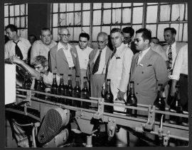 Grupo observando la fase final en la produccion de ron en Arecibo. (Foto vía Biblioteca Digital Puertorriqueña, Recinto de Río Piedras de la Universidad de Puerto Rico)