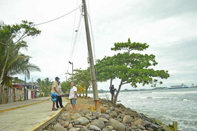 Reynaldo Charles y Ezequiel Hudson conversan con Eliécer Quesada (de izquierda a derecha) sobre el estado del rompeolas en que están parados. Esta es la parte más cercana entre las olas y las casas y en mareas altas, el agua atraviesa la nueva ciclovía y la calle y llega a las viviendas, en la comunidad de Cieneguita, en la costa del Caribe de Costa Rica. Crédito: Diego Arguedas/IPS