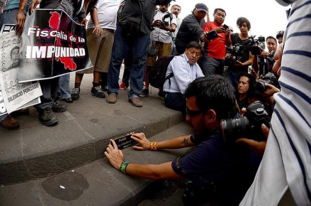 El fotógrafo mexicano Rubén Espinosa coloca una placa en honor de Regina Martínez, el 28 de abril de 2015, en la plaza central de Xalapa, la capital del sureño estado de Veracruz, para conmemorar los tres años del asesinato de la periodista. En julio de ese año, Espinosa fue asesinado también. Crédito: Roger López/IPS