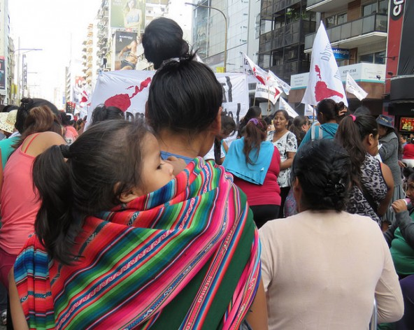 Una migrante de un país andino, con su hija cargada a sus espaldas, reivindica sus derechos con otras mujeres de igual condición, dentro de una manifestación en Buenos Aires, el 24 de marzo, por la verdad y la memoria, en conmemoración del golpe militar en Argentina, en 1976, que impuso hasta 1983 una cruenta dictadura. Crédito: Fabiana Frayssinet/IPS