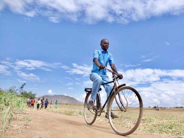 El asistente de Vigilancia de la Salud, Noah Chipeta, se traslada en bicicleta desde de la comunidad de Chanthunthu al centro de salud más cercano, a 17 kilómetros, para reabestecer el botiquín de medicamentos de la clínica rural del distrito de Kasungu, en Malawi. Crédito: UNICEF.