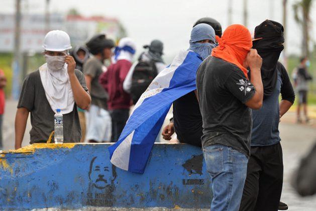 Jóvenes manifestantes nicaragüenses ocultan sus rostros detrás de una barricada en el sur de Managua, levantada con un muro en el que está impresa una imagen del presidente Daniel Ortega. La represión contra las protestas suma ya 131 personas muertas. Crédito: Jader Flores/IPS