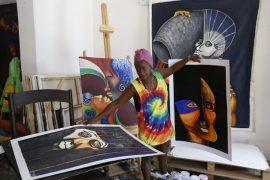 Myrna Padrón, promotora del proyecto autónomo y comunitario Casa Tomada Mirarte, organiza algunas obras de la artista Daimy Izquierdo, que muestran rostros y cuerpos con los rasgos propios de la población afrodescendiente, en su vivienda en La Habana, en Cuba. Crédito: Jorge Luis Baños/IPS